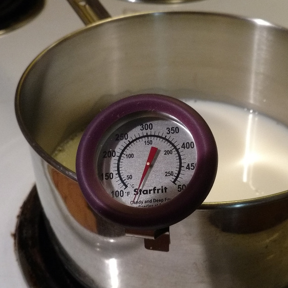 Milk heating on stove with thermometer